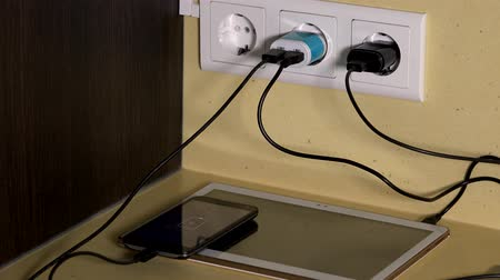 energized : woman hands attach micro usb cables to smart phones and tablet charging