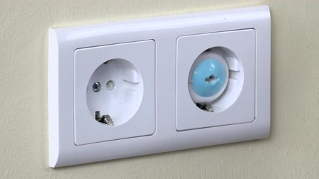 receptacle : Hands install safety plugs in electricity outlet on wall
