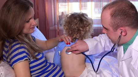 просмотров : Pediatrician checks breath stethoscope a little girl in the arms of mother