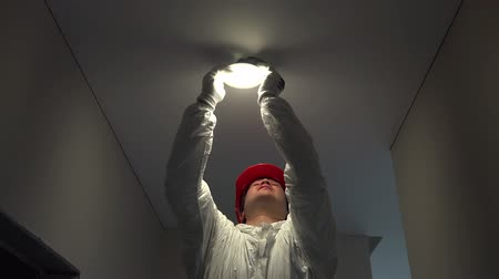 foglalat : professional electrician man mount circle led light into ceiling hole Stock mozgókép