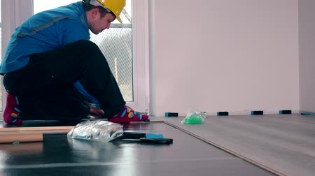 устанавливать : worker master in blue work wear install the laminate floor