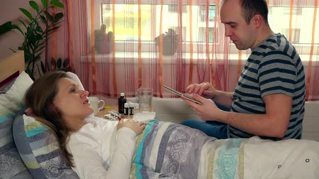 horečka : man husband with tablet computer entertain his sick wife woman in bed