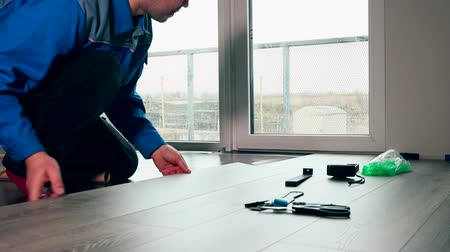 устанавливать : Worker in blue work wear laid wood floor in white room.
