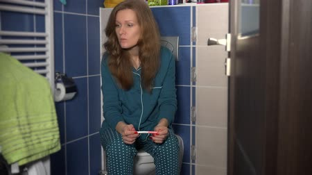 pizsama : young female in pajamas looking at pregnancy test sitting in bathroom