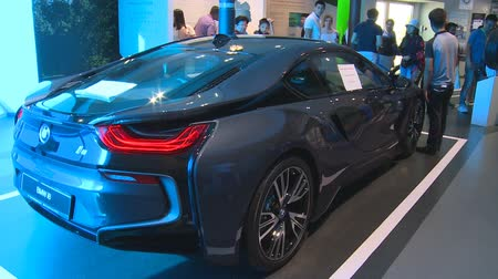 ASTANA, KAZAKHSTAN - July 8, 2017: new hybrid BMW i8 automobile car and people in Germany pavilion in Expo 2017. Handheld shot Stock Footage