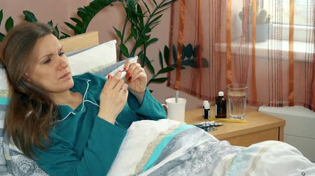 doente : Sick woman measure her temperature with electronic thermometer lying in bed