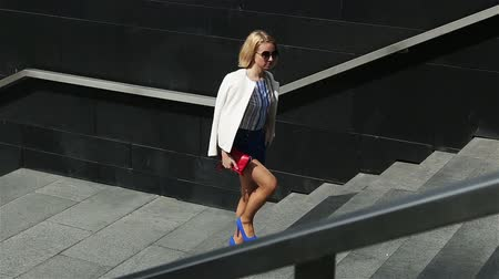 schody : young business woman in short blue trunks up the stairs