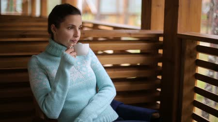 pulóver : girl in a blue sweater sitting on a wooden chair and drinking tea Stock mozgókép
