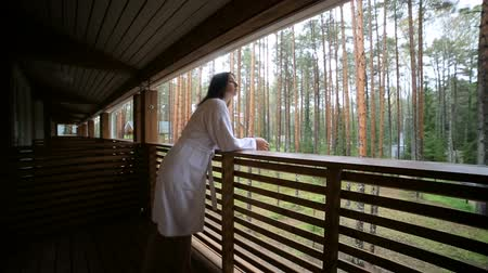goes : young girl goes to the balcony in white Bathrobe