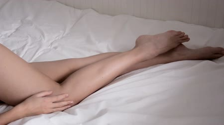 smyslnost : Nude female legs young girl lying in a white bed in the daylight