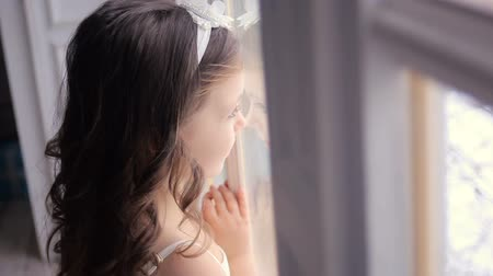 preso : little girl three years old in a white dress and with long hair looking out the window