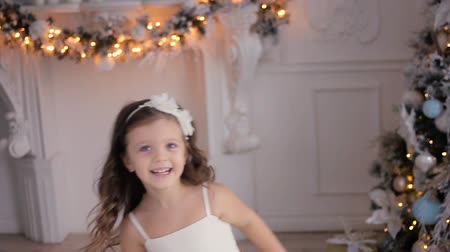 hides : little girl three years old in a white dress runs and hides at the Christmas tree