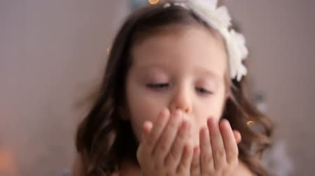 darbe : little girl three years blowing on silver sequins with hands forward Stok Video