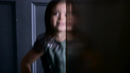 hides : little girl three years old in a green dress runs and hides Stock Footage