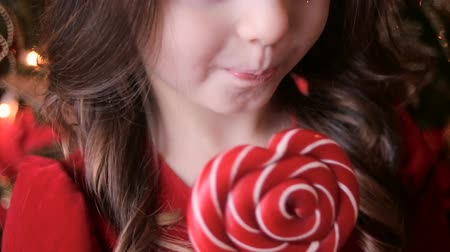 lambida : little girl three years in a red dress licks a great round colorful candy Vídeos