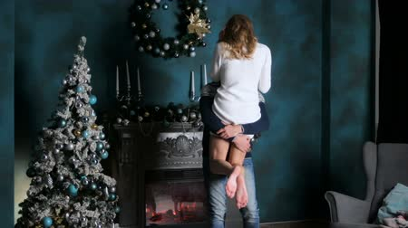 pulóver : guy with the girl in the sweater in the blue room with a festive Christmas tree