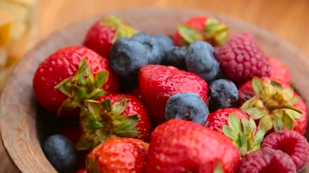 close up shot : fresh berries , strawberries, raspberries, blueberries in a copper bowl standing on a wooden table