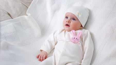 milestone : baby girl white knitted jacket with pink rabbit and a white hat lies on bed Stock Footage