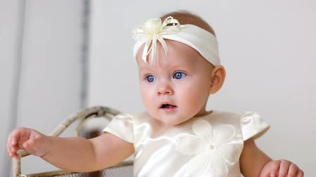 headband : baby girl in white dress and headband sitting on a little iron bed