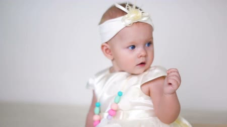 headband : baby girl in white dress and headband sitting on the wooden floor
