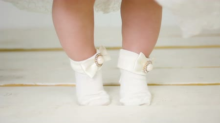 baby chubby : childs feet in a beautiful white socks on a wooden floor