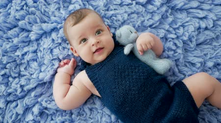 вязание : baby in a blue knitted jumpsuit clothes lying on blue fur Стоковые видеозаписи