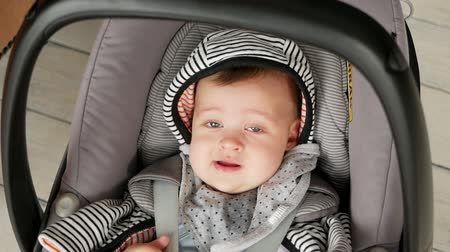 carseat : baby boy swinging in the car seat cradle Stock Footage