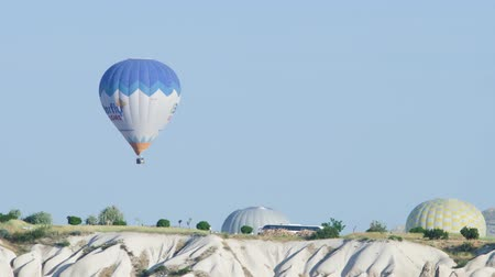 Turkey, Cappadocia - 7 June 2019: Hot air balloon striped with a basket of tourists flying high in the sky on Cappadocia Turkey June 7, 2019