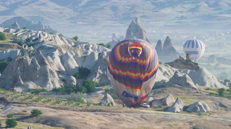 Turkey, Cappadocia - 7 June 2019: folding a large multi-colored balloon standing on the ground on Cappadocia Turkey June 7, 2019 Stock mozgókép