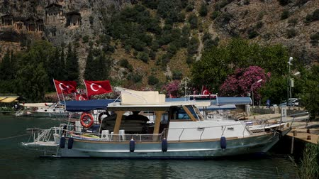 турецкий : Dalyan, Turkey - 9 June: boat with roof floating on the river in Dalyan Turkey on a summer day June 9, 2019 Стоковые видеозаписи