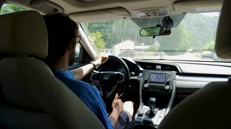 Antalya, Turkey - 9 June: man cabbie in a blue shirt and glasses drives a car on a hot summer day June 9, 2019