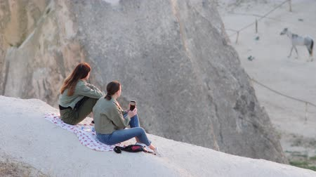 Turkey, Cappadocia - 7 June 2019: two girls sit on a white rock waiting for the launch of balloons June 7, 2019 Stock mozgókép