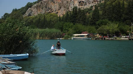 kürek çekme : Dalyan, Turkey - 9 June: young girl Mike carries tourists on a rowing boat on the river in the summer near the Lycian tombs June 9, 2019 Stok Video