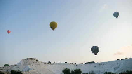 formations : Turkey, Pamukkale - 12 June 2019: Hot air colorful balloon fly over the white limestone mountains in the morning on a warm summer day June 12, 2019 Stock Footage