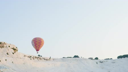 sobre o branco : Turkey, Pamukkale - 12 June 2019: Hot air colorful balloon fly over the white limestone mountains in the morning on a warm summer day June 12, 2019 Vídeos