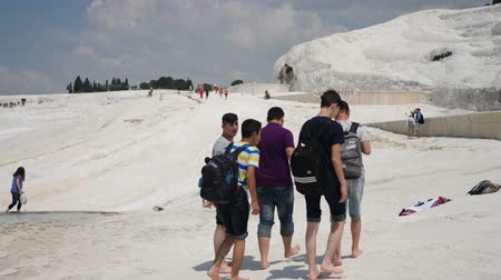 török : Pamukkale, Turkey - 9 June: lot group of tourists is on the slope of the white mountain in Sunny weather June 9, 2019