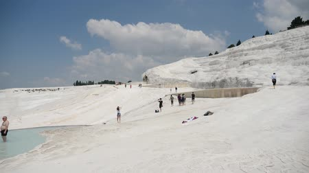 явление : Pamukkale, Turkey - 9 June: lot group of tourists is on the slope of the white mountain in Sunny weather June 9, 2019