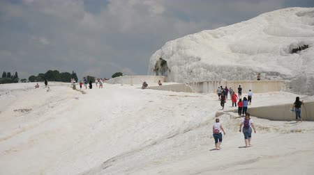 fenomen : Pamukkale, Turkey - 9 June: lot group of tourists is on the slope of the white mountain in Sunny weather June 9, 2019