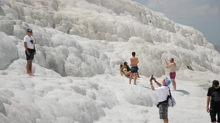 formations : Pamukkale, Turkey - 9 June: lot group of tourists is on the slope of the white mountain in Sunny weather June 9, 2019