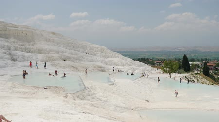Pamukkale, Turkey - 9 June: lot group of tourists is on the slope of the white mountain in Sunny weather June 9, 2019