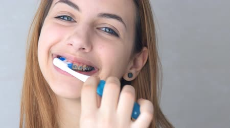 braces on teeth : Beautiful smiling girl with retainer for teeth brushing teeth. Stock Footage