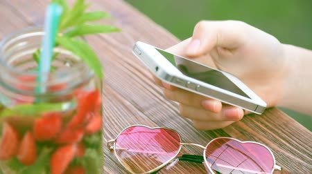 limonada : Girl using a cell phone outdoors.