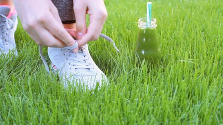 tying : Fruit smoothie and young girl lacing running shoes before workout. Stock Footage