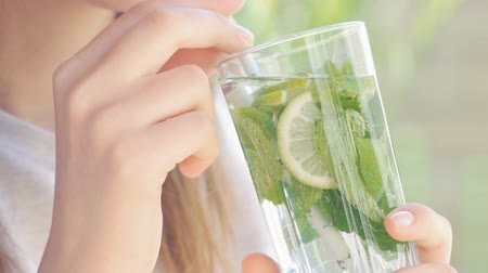 fodormenta : Young woman drinking lime and mint detox water. Stock mozgókép