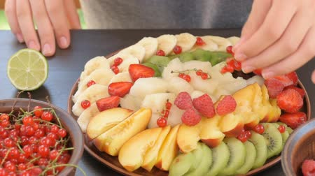 nektarinka : Hands serving fruit and berry plate. Exotic summer diet.