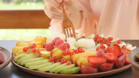 строгий вегетарианец : Young woman eating fruits salad. Exotic summer diet.