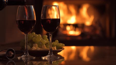 barmetro : Pouring a glass of red wine over a fireplace background.