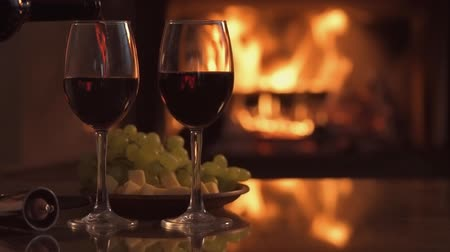 barmetro : Cinemagraph - Pouring a glass of red wine over a fireplace background. Motion Photo.