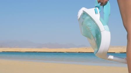 womans hand : Womans hand holds mask for diving. Vacation on beach. Ras Mohammed National Park in Egypt.