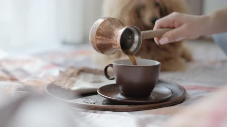 turk : Young woman is resting with a dog on the bed at home and pouring coffee into a cup. Breakfast.